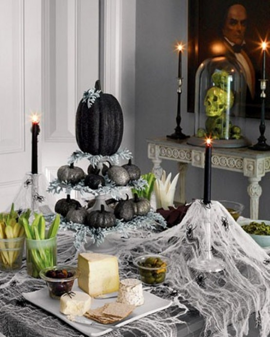 cheesecloth, black candles, a tiered stand with black and silver glitter pumpkins plus some greenery for a Halloween party