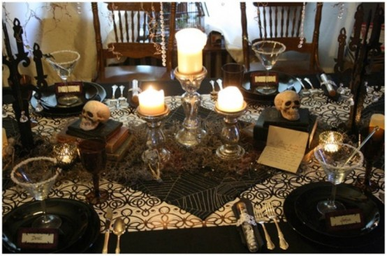 a black and white Halloween tablescape with black plates, printed textiles, candles, skulls, spiderwebs and black candelabras