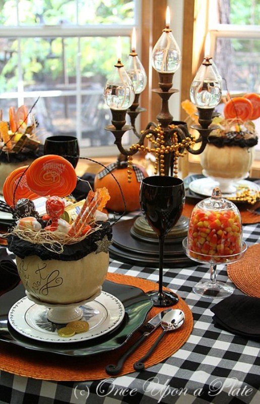 a bright Halloween tablescape in black, orange, white, with a candelabra, black goblets, orange pumpkins and plaid textiles