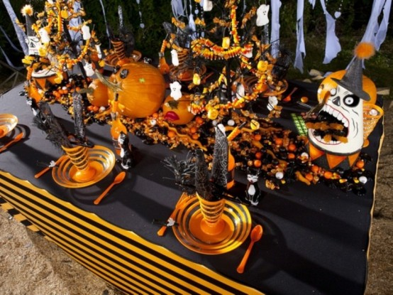 an extra bright blakc, graphite grey and orange Halloween tablescape with orange plates, cutlery, scary pumpkins and faces, lots of candies and witches' hats