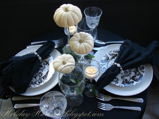 an elegant modern black and white Halloween tablescape with printed plates, black linens, white pumpkins and candles