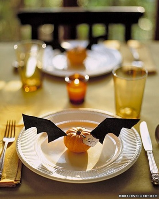 a cozy rustic Halloween tablescape with white plates, silver cutlery, mustard glasses, orange candles, pumpkins with bat wings