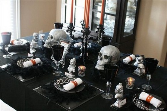 a black and silver Halloween table with black linens, plates and goblets, skulls, candles, a black candelabra with orange candles