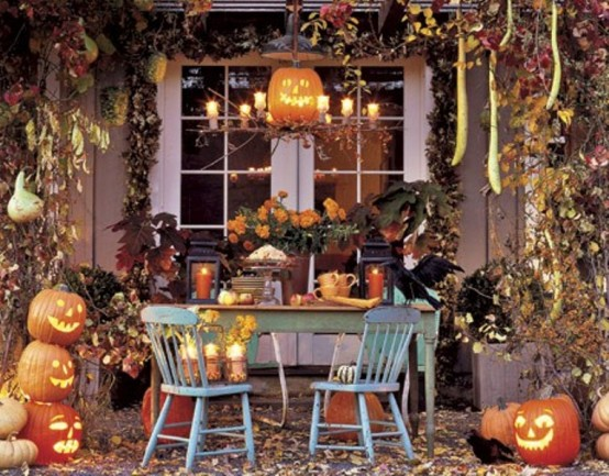 rustic Halloween table decor done with candle lanterns, crows, pumpkins and jack-o-lanterns, fall leaves and lights