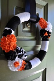 a bold Halloween wreath in black and white, with black, white and orange fabric flowers is a cool idea for Halloween