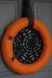 a bright Halloween wreath of an orange form, with a black spider net inside and some faux spiders on the wreath is Halloween classics
