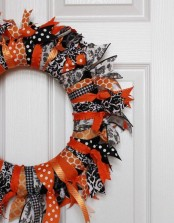a bold black, orange and white Halloween wreath of fabric stripes only is a great way to upcycle some old fabric you have and get a cool seasonal decoration