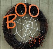 a stylish Halloween wreath of vine,w ith orange letters, a spider net and a large and bold spider is a geat idea for Halloween