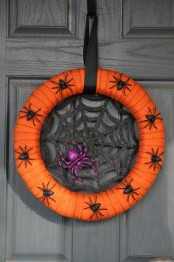 a bold and pretty Halloween wreath of an orange form, a glitter spider net, a purple glitter spider and some black mini spiders on the wreath form