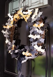 a Halloween wreath of vine covered with black, orange and white paper bats all over is a lovely idea that can be easily DIYed