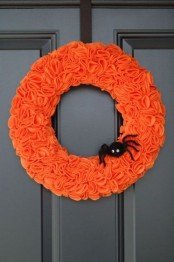an orange fabric wreath with a black spider is a colorful and pretty decoration for Halloween you can easily make