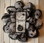 a whimsy black and white Halloween wreath covered with fabric and ribbons, with spiders and a sign with spider nets and spiders is a unique solution for decor