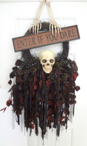 a Halloween wreath of vine, with ribbons, leaves, feathers, a skull and skeleton hands plus a sign on top