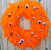 a bold orange feather wreath with googly eyes all over is a lovely and bright idea for Halloween decor