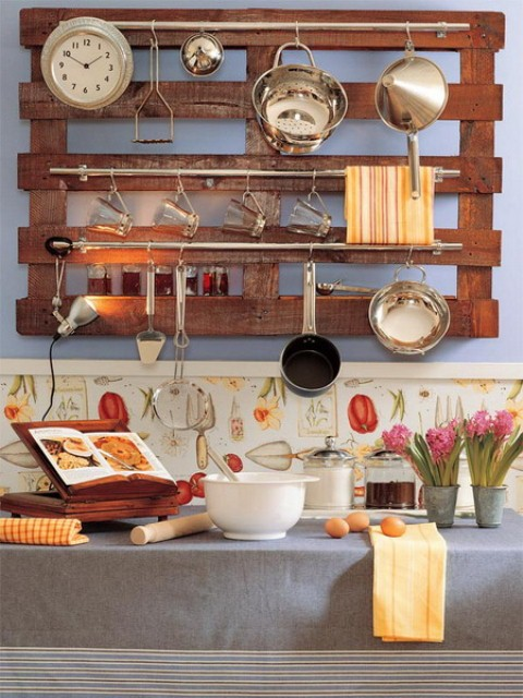 a wall-mounted pallet with railings that feature holders for all kinds of stuff, from clocks to utensils is a cool idea for a rustic space