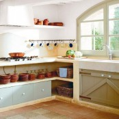 built-in kitchen furniture with open storage spaces for tableware and some drawers for storage is a great solution for a rustic space