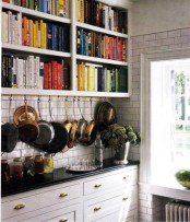 a large bookshelf with additional hooks for pans and pots is great for those who love reading while cooking or eating