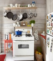 a rack with cups and mugs and hooks for hanging pots and pans that can be hung