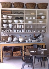 a large open wall-mounted shelf with baskets on top and an additional kitchen island with a storage space for holding a lot of things