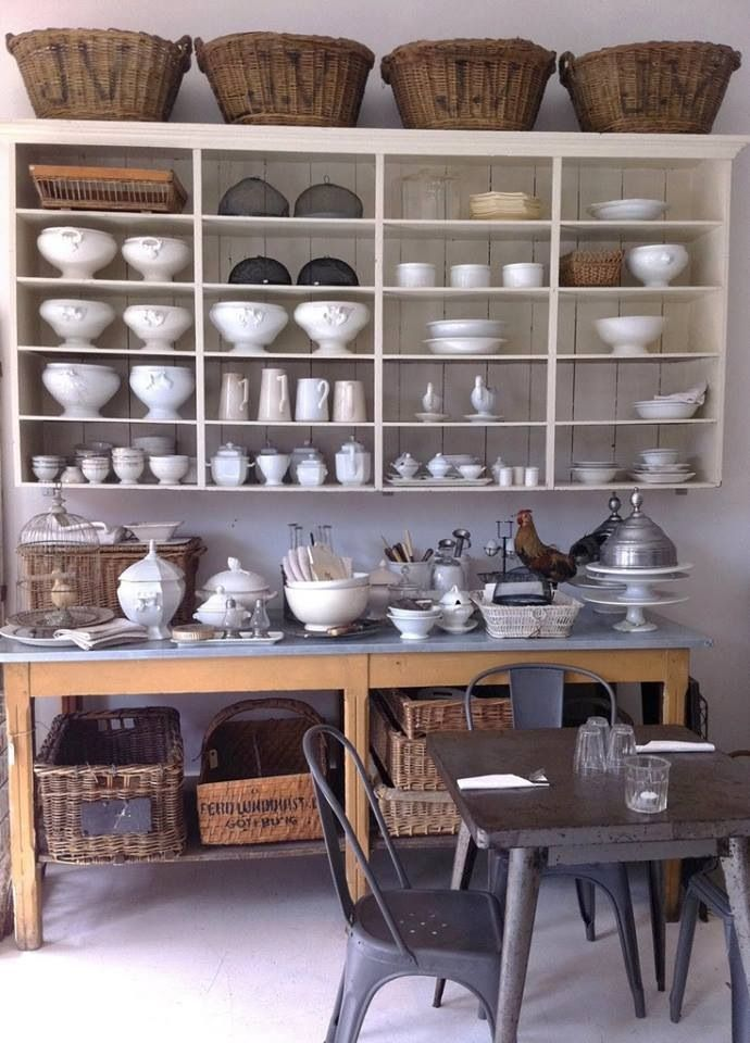 a large open wall mounted shelf with baskets on top and an additional kitchen island with a storage space for holding a lot of things