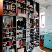 an oversized open shelving unit is used to separate the spaces and hold everything the owners may need, it's a great idea