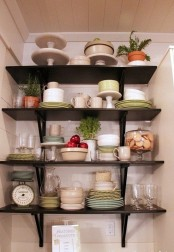 dark wall-mounted open shelves taking an awkward nook to make the maximal use of it