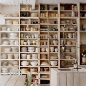 a whole wall covered with a large open storage unit for tableware is a great idea for any kitchen