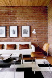a welcoming modern living room with a red brick statement wall, faux fur pillows and a wooden ceiling