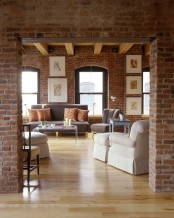 a chic living room with red brick walls highlighted with white grout and elegant upholstered furniture