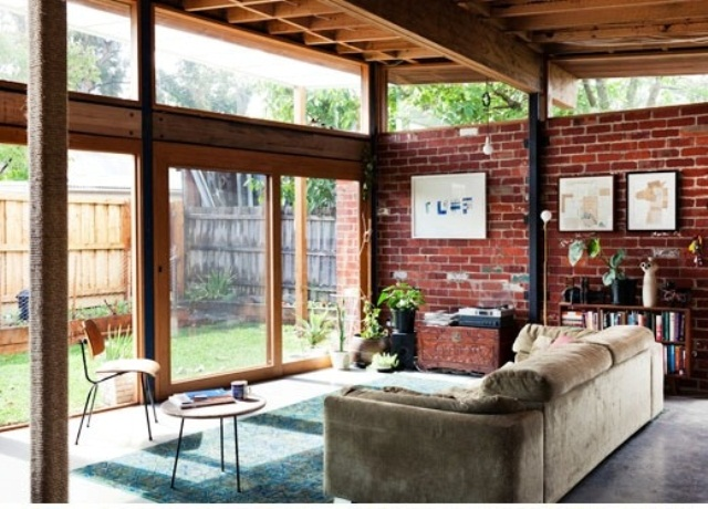 an indoor outdoor living room with a red brick statement wall and a glazed wall with sliding doors