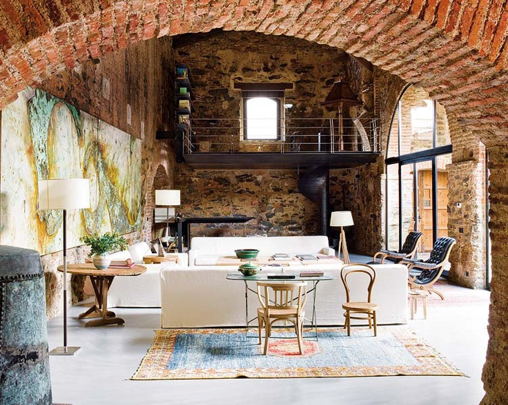 a vintage living room with a double height ceiling and original brick walls and touches of stone