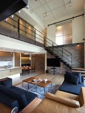 an open layout with a kitchen and living room plus a brick statement wall in muted shades that contrasts white surfaces
