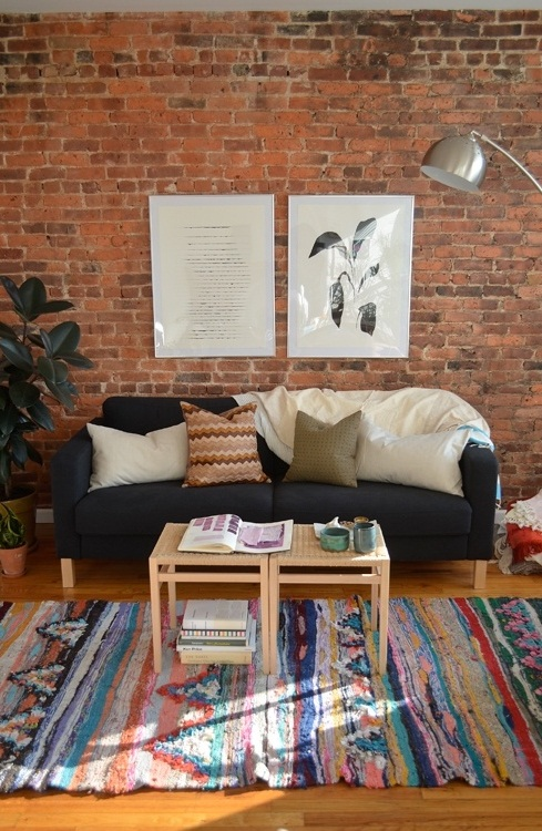 a bright boho living room with a red brick wall that adds texture and interest to the space
