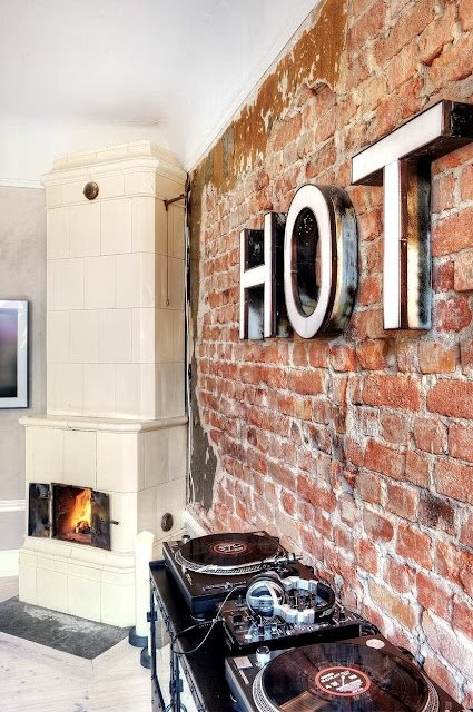 a statement red brick wall with modenr letters and a large stove for more contrast