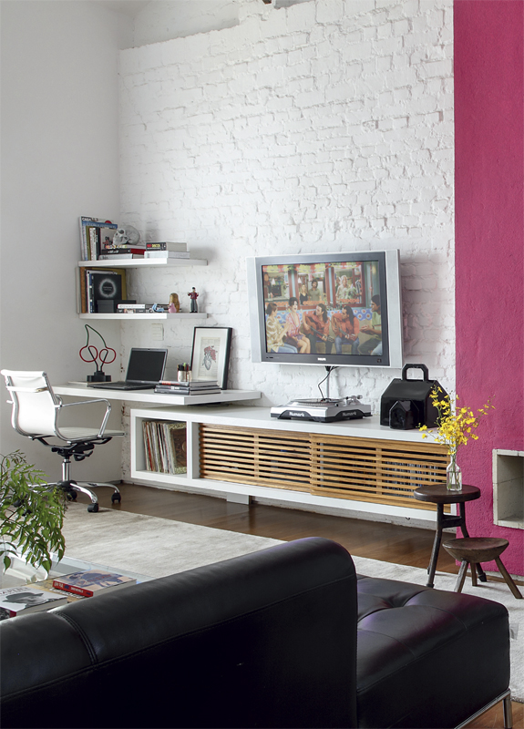 a contemporary living room with a white brick wall and a fuchsia accent plus dramatic dark furniture