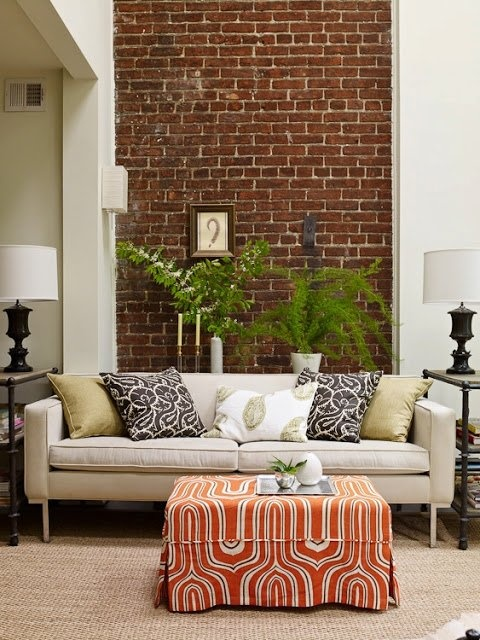 an eclectic living room with a dark brick statement wall that contrasts the white surfaces