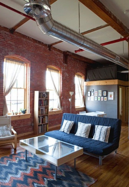 an industrial living room done with red brick walls and metal pipes on the ceiling plus mid-century modern furniture