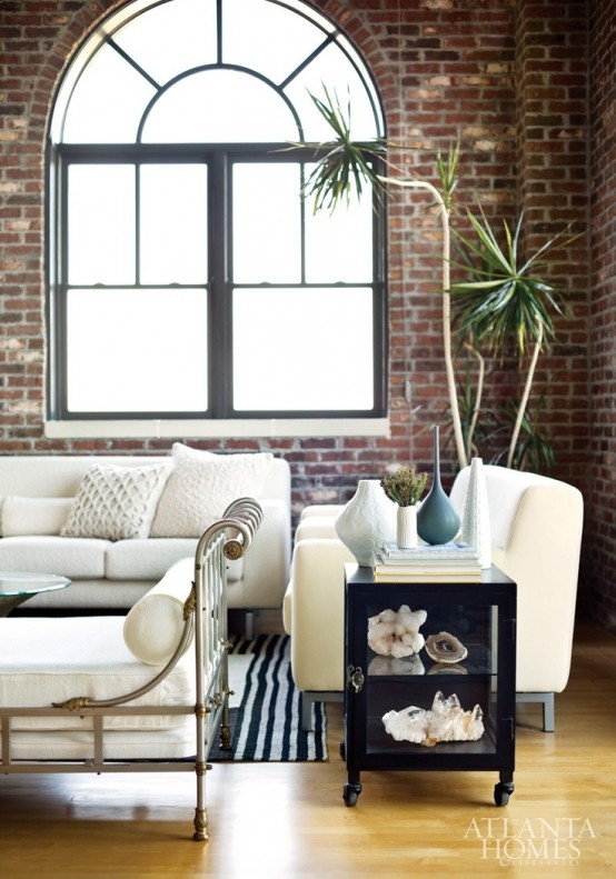 a chic living room with red brick walls and elegant white upholstered furniture for a contrasting combo