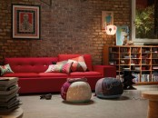 a bright contemporary living room with a red brick wall and vibrant furniture and artworks