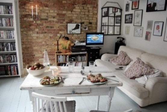 a neutral eclectic space done with a red brick statement wall that adds color to it