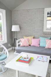 a chic neutral space with a grey brick accent wall and pastel touches and furniture
