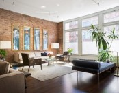 a contemporary living room with a red brick statement wall and a matching rich stained wooden floor