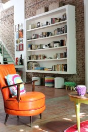a living room with original brick walls, colorful items and accents plus artworks