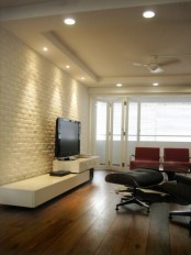 a minimalist living room in black, white and red and with white brick walls for a texture