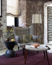 a chic living room with red brick walls and white grout, contemporary furniture and Roman shades
