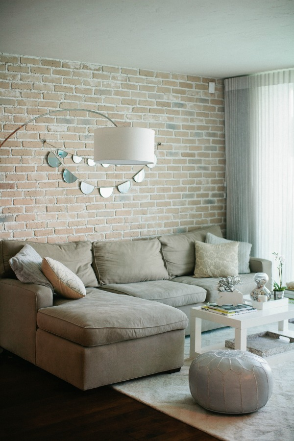 a neutral living room with muted brick walls that bring texture and interest to the space, with shiny touches nd a leather ottoman