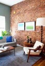 an eclectic living room with a statement red brick wall and colorful touches and artworks