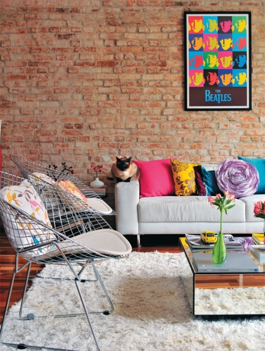 an eclectic living room with a red brick statement wall, colorful pillows and artworks