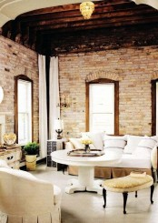 a refined vintage living room with elegant furniture and whitewashed brick walls and a wooden ceiling for a vintage feel