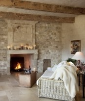 a French farmhouse living room with a statement white brick wall and a built-in fireplace
